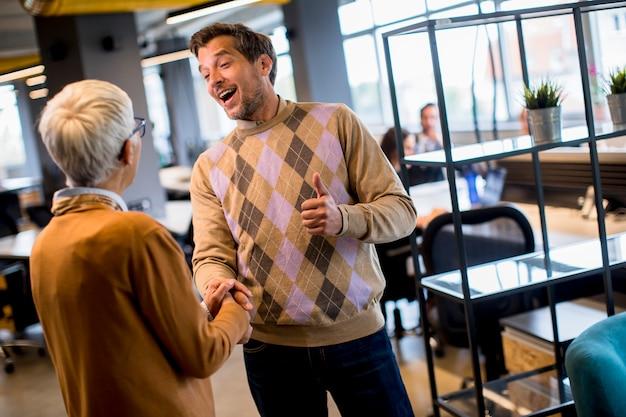 Jonge zaken man en senior zaken vrouw handen schudden in het kantoor