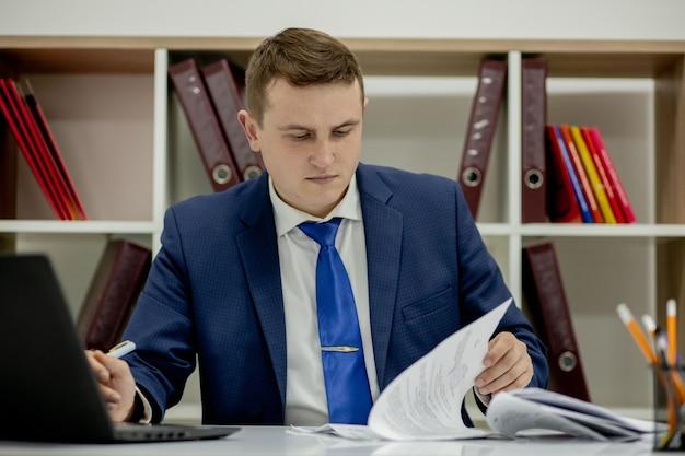 Jonge zaken man werken met documenten kijken door papieren in de map, zit op kantoor.
