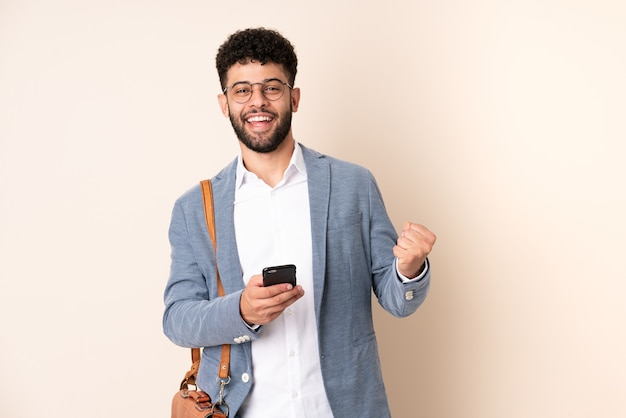 Jonge zaken marokkaanse man geïsoleerd op beige achtergrond met telefoon in overwinning positie