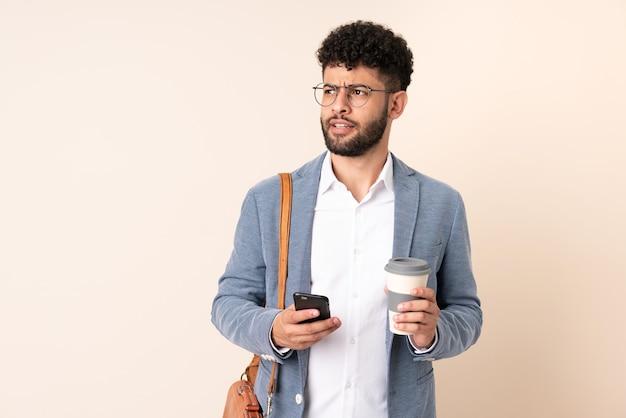 Jonge zaken marokkaanse man geïsoleerd op beige muur met koffie om mee te nemen en een mobiel terwijl hij iets denkt