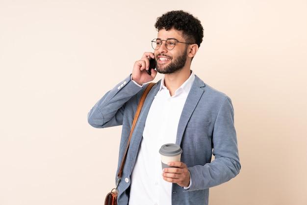 Jonge zaken marokkaanse man geïsoleerd op beige muur met koffie om mee te nemen en een mobiel