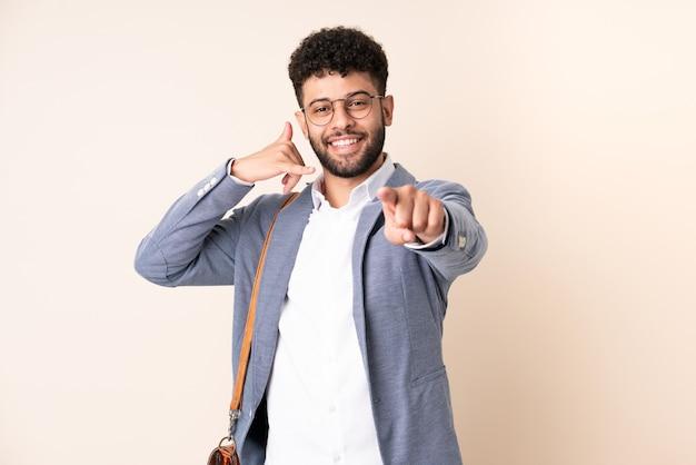 Jonge zaken marokkaanse man geïsoleerd op beige muur telefoongebaar maken en naar voren wijzen