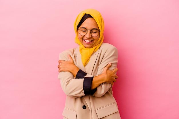 Jonge zaken moslimvrouw geïsoleerd op roze achtergrond knuffels, zorgeloos en gelukkig glimlachen.