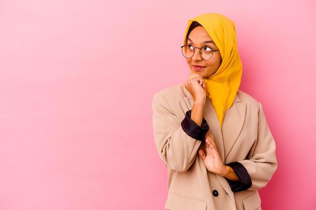 Jonge zaken moslimvrouw geïsoleerd op roze achtergrond op zoek zijwaarts met twijfelachtige en sceptische uitdrukking.