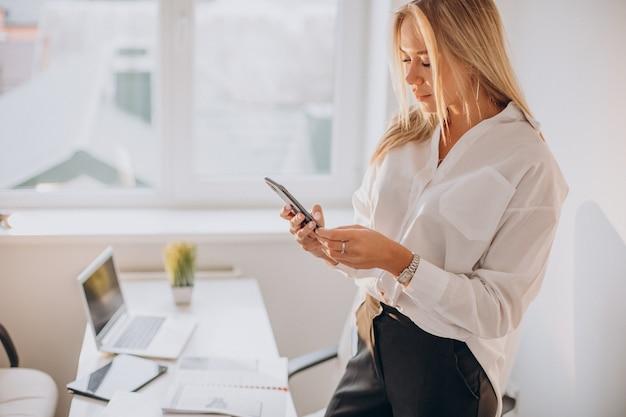 Jonge zaken vrouw met telefoon in kantoor