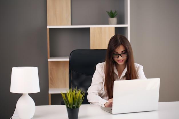 Jonge zaken vrouw werkt in haar kantoor met behulp van een laptop