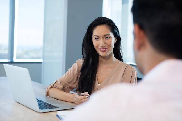 Jonge zaken vrouw zitten met mannelijke collega in kantoor