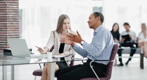 Jonge zakencollega's die achter een bureau praten
