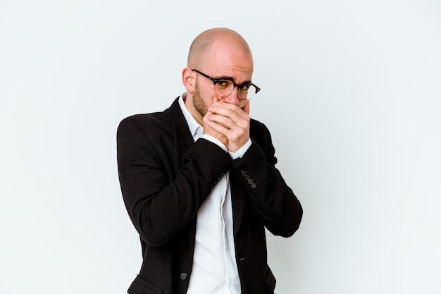 Jonge zakenkaukasische kale man geïsoleerd op een blauwe achtergrond die de mond bedekt met handen die zich zorgen maken.