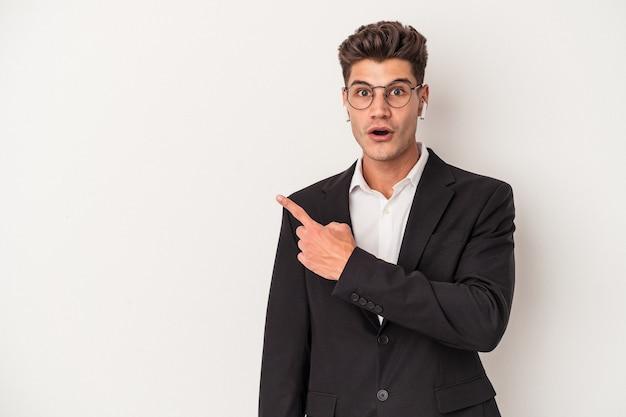 Jonge zakenkaukasische man met een koptelefoon op een witte achtergrond die naar de zijkant wijst