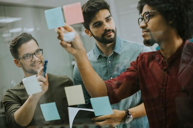 Jonge zakenlieden die voor glasmuur bespreken die post-itnota's en stickers gebruiken