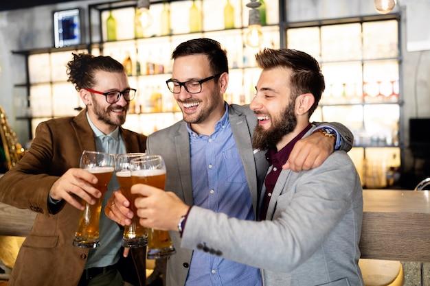 Jonge zakenlieden drinken bier, praten en glimlachen terwijl ze uitrusten in de pub