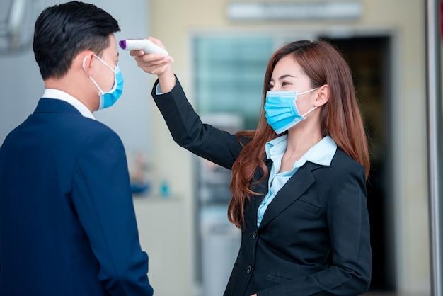 Jonge zakenlieden gebruiken thermometers om de lichaamstemperatuur te meten nadat het covid-19-virus zich heeft verspreid om de verspreiding van ziektekiemen en bacteriën te voorkomen.