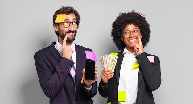 Jonge zakenlui die gelukkig glimlachen en dagdromen of twijfelen, op zoek naar de kant. humoristisch bedrijfsconcept