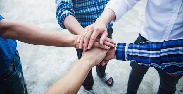 Jonge zakenlui die hun handen samenbrengen