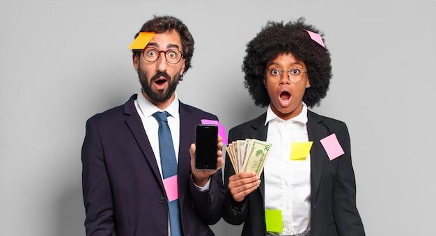 Jonge zakenlui kijken erg geschokt of verrast, starend met open mond en zegt wow. humoristisch bedrijfsconcept