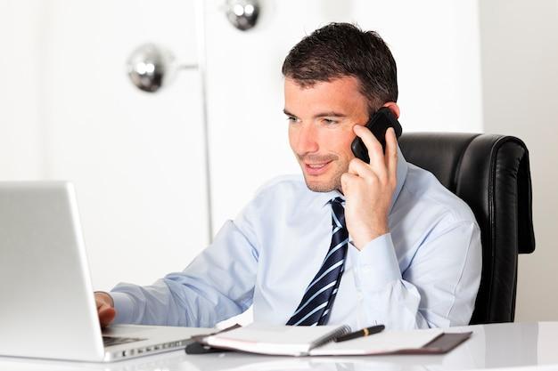 Jonge zakenman aan de telefoon in kantoor