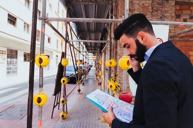 Jonge zakenman aan het werk en aan het praten over de telefoon