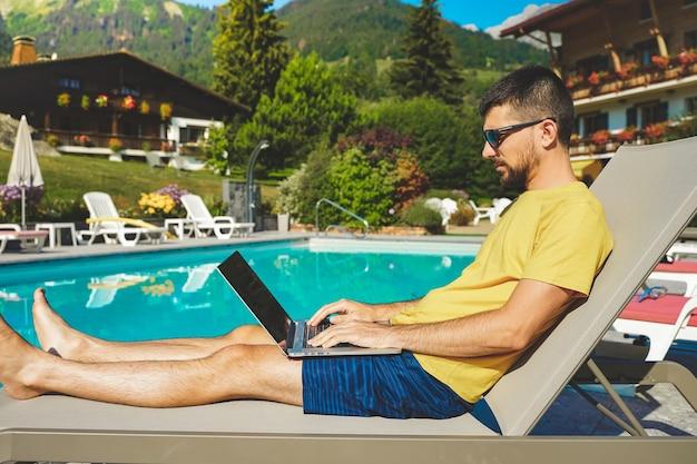 Jonge zakenman aan het werk met laptop op prachtige schilderachtige bergachtergrond