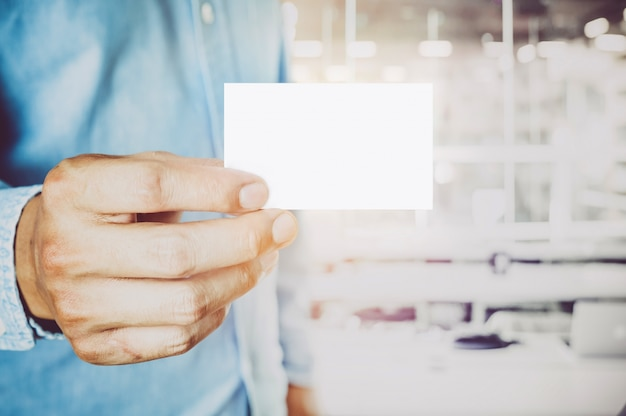 Jonge zakenman bedrijf wit visitekaartje op moderne kantoor vervagen achtergrond.