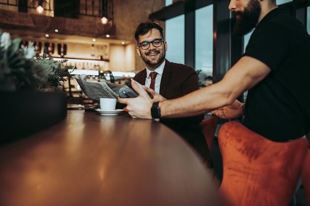 Jonge zakenman betalen met contactloze creditcard met nfc-technologie.