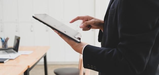 Jonge zakenman bezig met zijn project tijdens het gebruik van tablet