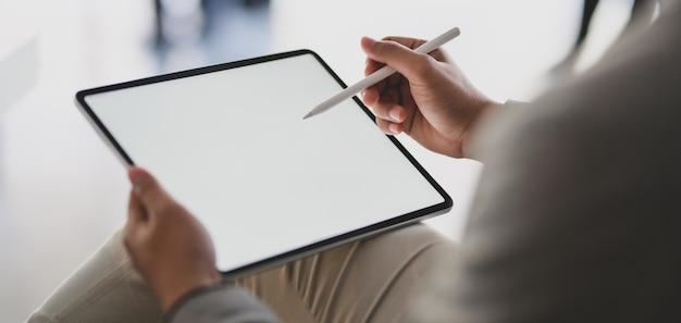 Jonge zakenman bezig met zijn project tijdens het schrijven op een leeg scherm tablet