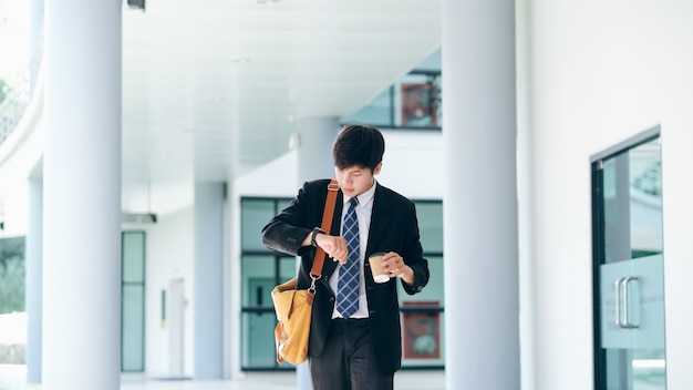 Jonge zakenman bezorgd op zoek naar zijn polshorloge.