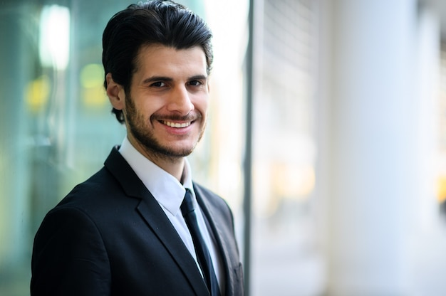 Jonge zakenman buiten glimlachend vol vertrouwen