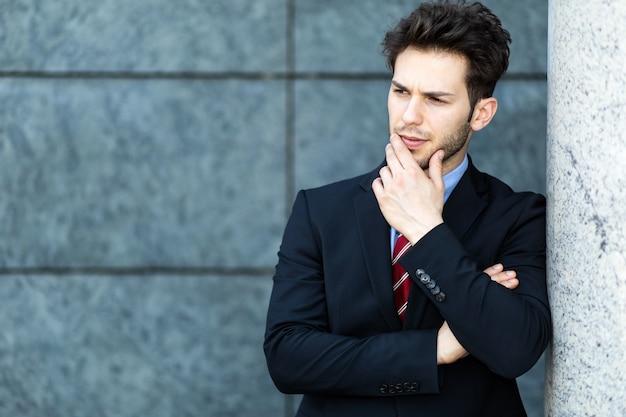 Jonge zakenman buiten in een peinzende uitdrukking