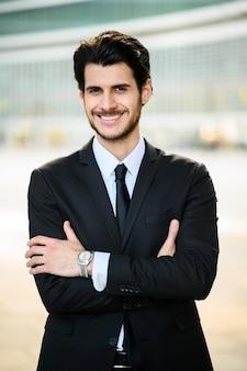 Jonge zakenman buiten vol vertrouwen glimlachen