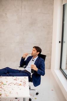 Jonge zakenman champagne drinken op kantoor na het kerstfeest