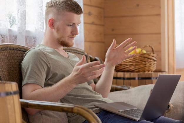 Jonge zakenman communiceert met werknemers met behulp van een laptop op afstand van huis
