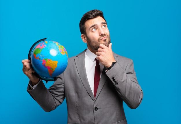 Jonge zakenman denkt, voelt zich twijfelachtig en verward, met verschillende opties, zich afvragend welke beslissing hij moet nemen met het vasthouden van een wereldbolkaart