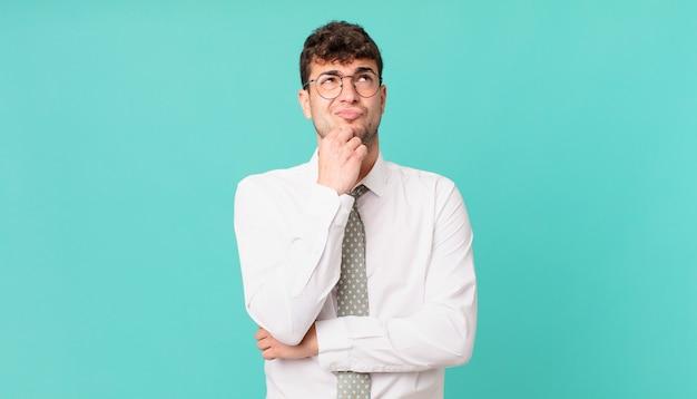 Jonge zakenman denkt, voelt zich twijfelachtig en verward, met verschillende opties, zich afvragend welke beslissing hij moet nemen