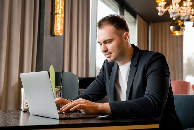 Jonge zakenman die aan laptop in moderne koffie in hotel werkt