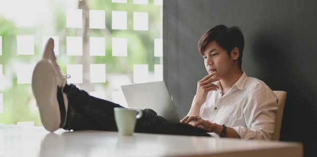 Jonge zakenman die aan zijn project met laptop computer werkt terwijl het zetten van de voeten op lijst