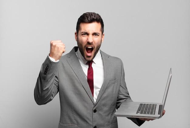 Jonge zakenman die agressief met een boze uitdrukking of met gebalde vuisten schreeuwt die succes viert en laptop houdt