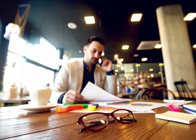 Jonge zakenman die bedrijfsresultaten over de mobiele telefoon analyseert. focus op bril, met wazig man op achtergrond.