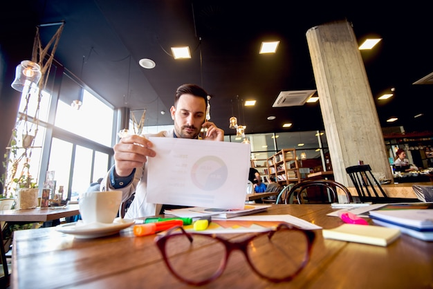 Jonge zakenman die bedrijfsresultaten over de mobiele telefoon analyseert.