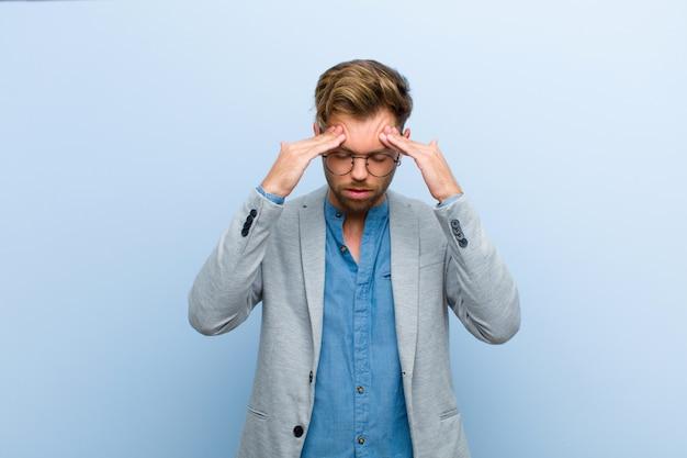 Jonge zakenman die beklemtoond en gefrustreerd kijkt, werkend onder druk met hoofdpijn en verontrust met problemen tegen blauwe achtergrond