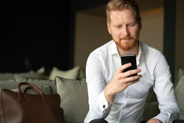 Jonge zakenman die bericht met mobiele telefoon verzendt. zaken, technologie, mensenconcept