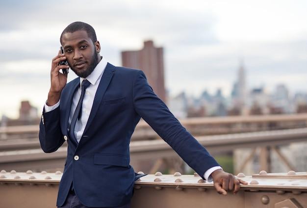 Jonge zakenman die bij de telefoon op de brug van brooklyn spreekt. new york city.
