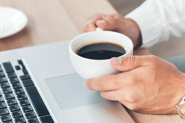 Jonge zakenman die bij laptop computer met hete in hand koffie werkt.