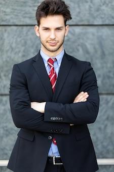 Jonge zakenman die buiten tegen een muur ligt
