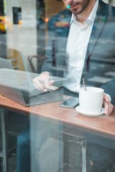 Jonge zakenman die creditcard gebruiken om rekening in koffie te betalen