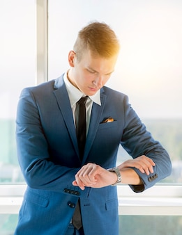 Jonge zakenman die de tijd controleert op polshorloge