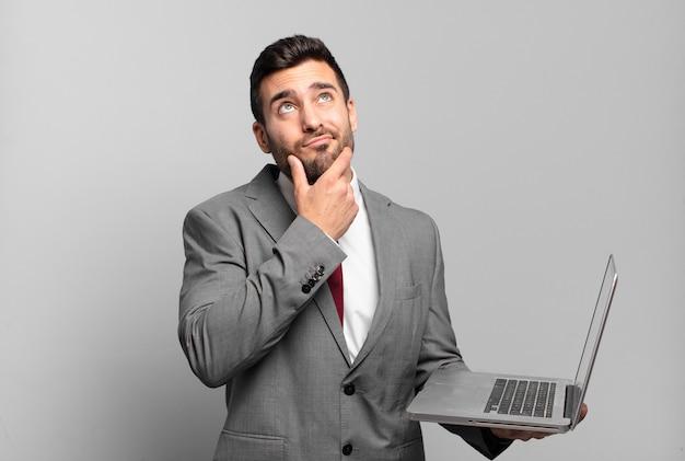 Jonge zakenman die denkt, twijfelachtig en verward voelt, met verschillende opties, zich afvraagt welke beslissing hij moet nemen en een laptop vasthoudt
