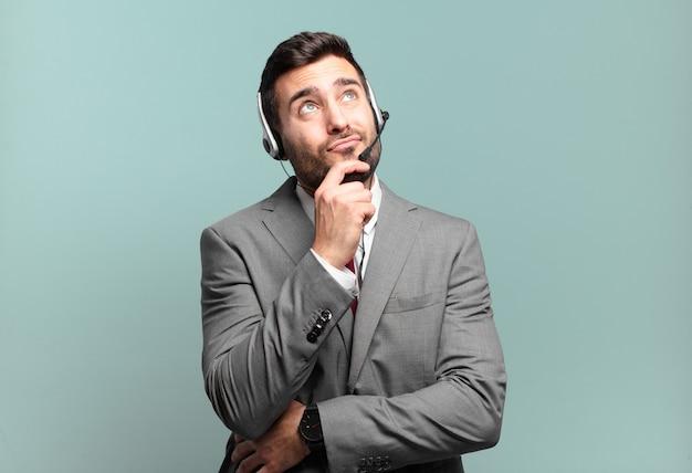 Jonge zakenman die denkt, zich twijfelachtig en verward voelt, met verschillende opties, zich afvragend welke beslissing hij een telemarketingconcept moet nemen