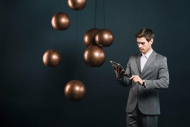 Jonge zakenman die digitale tablet bekijkt die zich dichtbij de moderne kroonluchter bevindt